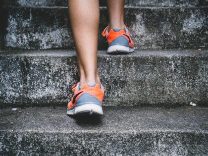 Image of two feet with running shoes walking up concrete stairs.