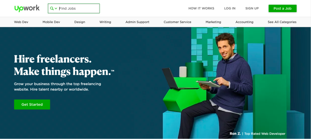 "Image of a man sitting on a blue-green box with captioning to the left in white lettering, ""Hire freelancers. Make things happen."" The background is dark green."